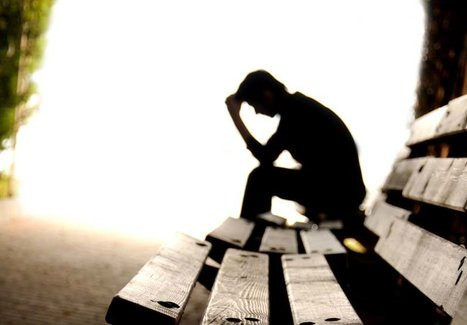 Photographie d'un homme assis sur un banc et visiblement absorbé par ses pensées.