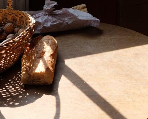 Photographie d'une table au soleil, sur laquelle sont posés un morceau de baguette et un panier rempli de noix avec un casse-noix.