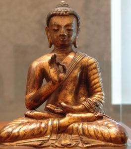 Photographie d'un statue représentant le Bouddha Amoghasiddhi, assis en position du lotus.