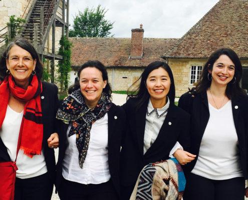 Photographie montrant quatre femmes souriantes se tenant par le bras.