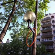 Photographie montrant un cerceau rouge accroché à un réverbère. À l'arrière plan on voit un arbre et des immeubles.