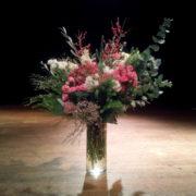 Photographie d'un bouquet de fleurs roses et blanches, dans un vase posé sur un parquet devant un fond noir et sous une lumière artificielle.