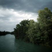 Photo d'un cours d'eau et de sa rive droite boisée sous un ciel nuageux