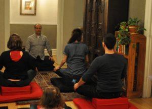 Photo de la salle de pratique de l'École occidentale de méditation, fondée par Fabrice Midal, à Montréal, avec, assis de face, Philippe Blackburn et quelques pratiquants de dos.