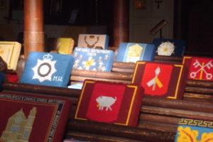 Photographie de bancs d'église en bois sur le dossier desquels des coussins colorés sont posés.