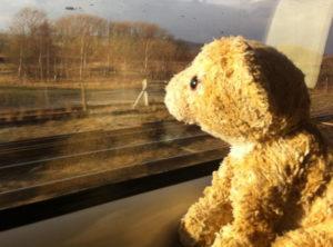 Photographie d'un ours en peluche assis dans un train et regardant par la fenêtre