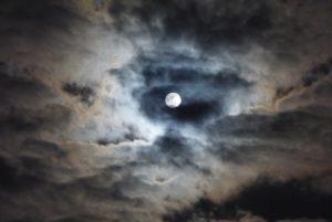 Photographie d'un ciel nuageux, une nuit de pleine Lune.
