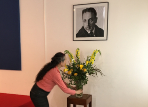 Photo de Catherine Mogenent plaçant un vase de fleurs sous un portrait de Rilke