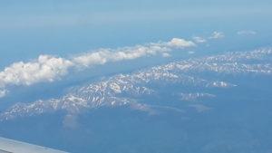 Photographie d'une chaine de montagnes surmontée d'une trâinée de nuages vus du ciel.