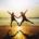 Photographie montrant deux enfants sautant devant un coucher de soleil. Leurs bras et leurs jambes s'unissent en forme de cœur.