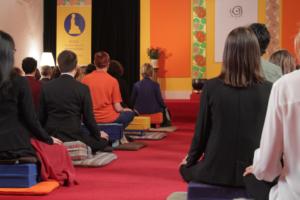 Groupe de personne vues de dos en train de pratiquer la méditation assise.