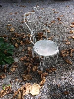 Photographie d'une chaise de jardin sur un sol gravillonné parsemé de feuilles mortes