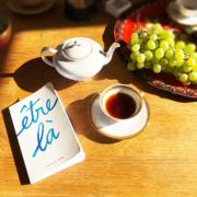 """Photographie montrant, disposés sur une table, une théière, une tasse de thé, une grappe de raisins sur un plateau et le livre """"Être là""""."""