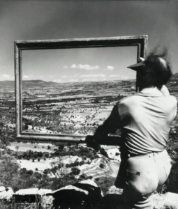 Photographie par Willy Ronis du peintre André Lhote vue de dos portant un cadre vide devant un paysage à Gordes.