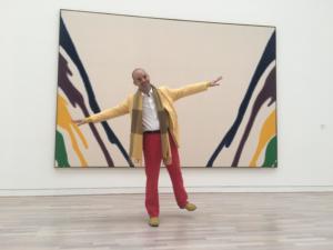 Photo de Fabrice Midal, fondateur de l'École occidentale de méditation, debout sur un pied, les bras à l'horizontale, souriant devant un tableau d'art moderne