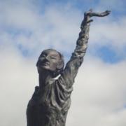 Photographie d'une statue de Barbara levant la mains au ciel
