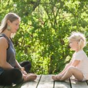 Photographie d'une femme et d'une petite fille assises en tailleur l'une en face de l'autre