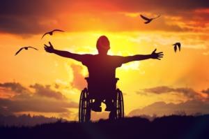 Photo d'un homme en chaise roulante ouvrant grand les bras face au soleil orangé