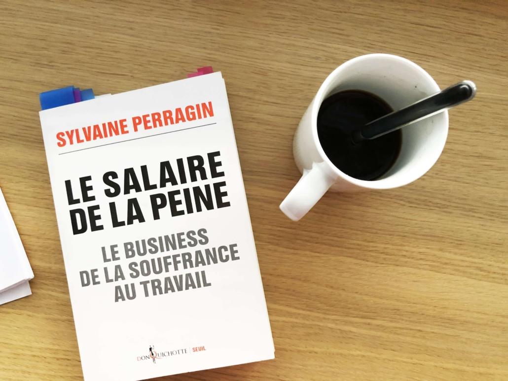 """Photo du livre de Sylvaine Perragin, """"Le salaire de la peine"""", posé sur une table à côté d'une tasse de café"""