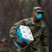 Photo d'un homme avec un masque respiratoire portant un paquet de papier toilette