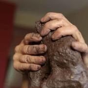 Photo des mains de Sylvie en train de scupter la terre