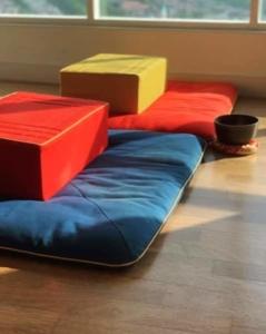 Image de tapis et coussins de méditation colorés, avec un petit gong