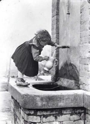 Enfant remplissant un pichet à eau à une fontaine, noir et blanc