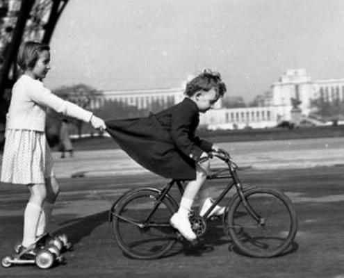 Photo noir et blanc de Robert Doiseau : un enfant en rolleur est tiré par un enfant à vélo en s'accrochant à sa jupe